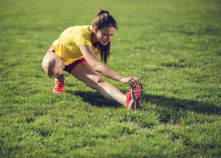 Young female athlete stretching her leg in nature.