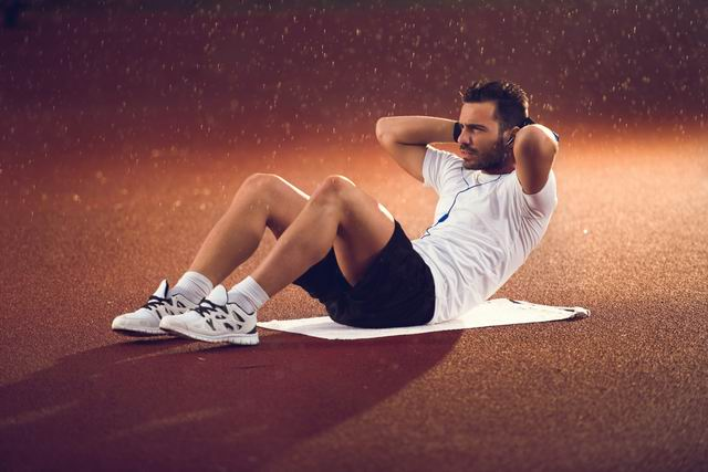 Athletic man doing sit-ups on a rain with hands behind his head.