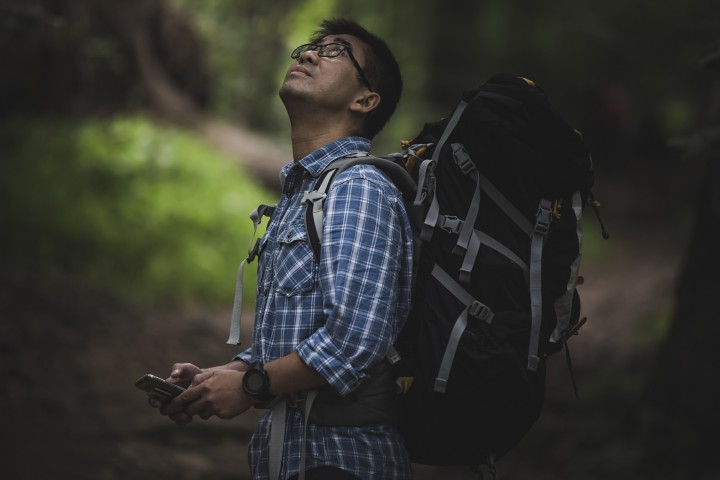 Hiker with backpack and smart phone, looking up