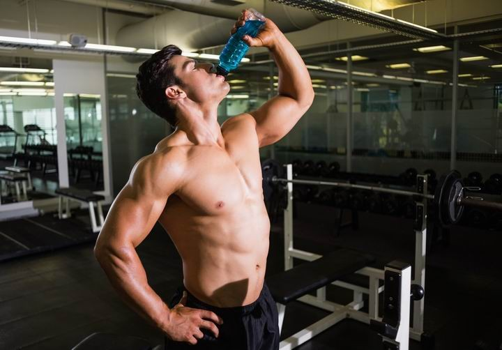 Shirtless muscular man drinking energy drink in gym